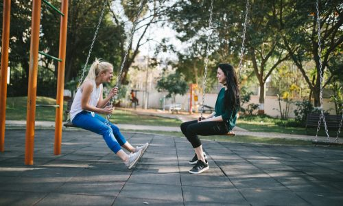 lesbian couple talking while on swing set at park