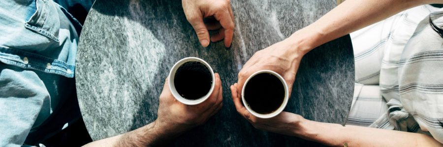 couple with coffee coaching each other
