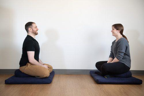 woman sitting on meditation cushion doing neuromeditation with Dr David Helfand PsyD